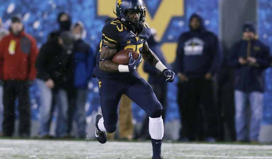 FILE - In this Nov. 19, 2016, file photo, West Virginia running back Justin Crawford (25) runs against Oklahoma during an NCAA college football game, in Morgantown, W.Va. West Virginia plays at Iowa State on Saturday. (AP Photo/Raymond Thompson, File)