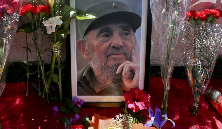 A portrait of Fidel Castro lays surrounded by flowers outside Cuba's embassy in Santiago, Chile, Saturday, Nov. 26, 2016, the day after he died. Castro, who led a rebel army to improbable victory, embraced Soviet-style communism and defied the power of 10 U.S. presidents during his half century rule of Cuba, died at age 90 in Cuba late Friday, Nov. 25. (AP Photo/Esteban Felix)