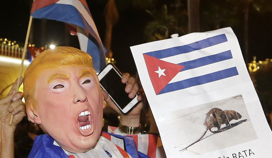 A person wearing a Donald Trump mask holds a sign in Spanish that reads the Rat Dies as he celebrates the death of Fidel Castro Saturday, Nov. 26, 2016, in the Little Havana area in Miami. Castro died eight years after ill health forced him to formally hand power over to his younger brother Raul, who announced his death late Friday, Nov. 25, on state television. (AP Photo/Alan Diaz)