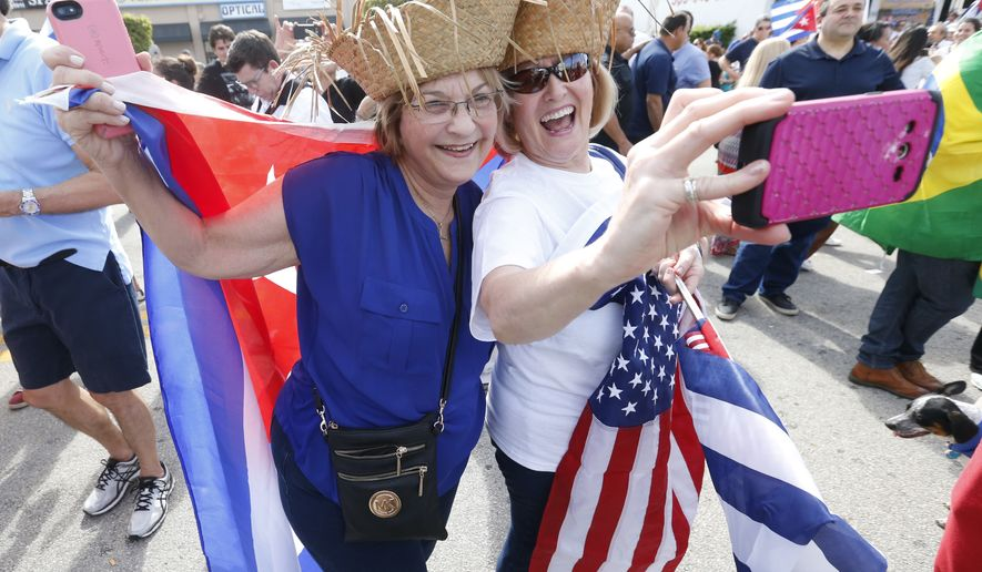 "Carmen Romanach, left, and Maria Gregorian take a selfie as they join members of the Cuban community as they react to the death of Fidel Castro, Saturday, Nov. 26, 2016, in the Little Havana area in Miami. ""We are not celebrating a death,"" said Romanach, ""We are celebrating a new hope for Cuba."" (AP Photo/Wilfredo Lee)"