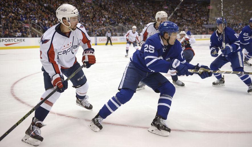 Toronto Maple Leafs' James van Riemsdyk, right, and Washington Capitals' Matt Niskanen chase the puck during the second period of an NHL hockey game in Toronto, Saturday, Nov. 26, 2016. (Jon Blacker/The Canadian Press via AP)