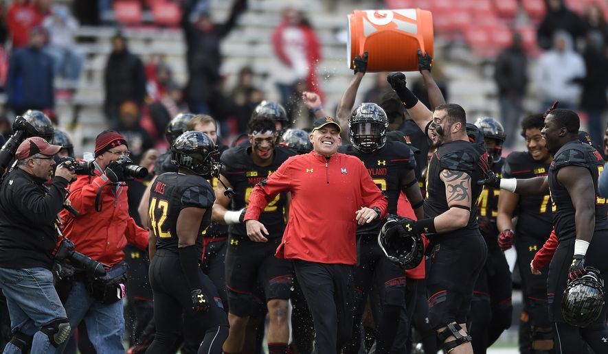 Maryland head coach DJ Durkin, center, runs away from his team after getting doused as they celebrate defeating Rutgers 31-13 in an NCAA college football game, Saturday, Nov. 26, 2016 in College Park, Md. (AP Photo/Gail Burton) **FILE**