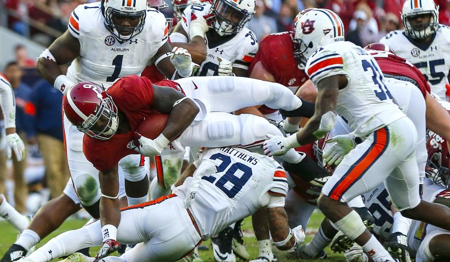 Alabama running back Bo Scarbrough (9) dives over for a first down during the first half of the Iron Bowl NCAA college football game against Auburn, Saturday, Nov. 26, 2016, in Tuscaloosa, Ala. (AP Photo/Butch Dill)