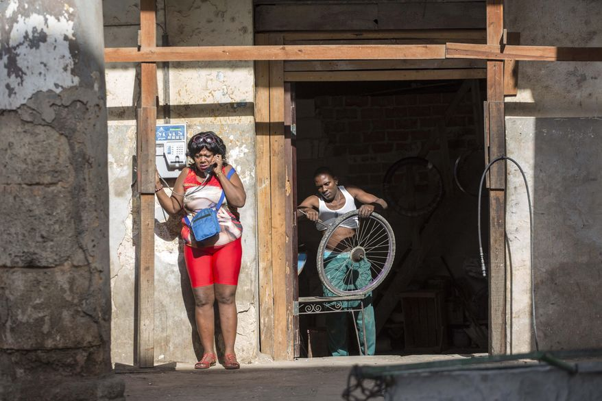 A woman speaks on a public telephone as a man repairs a wheel in Havana, Cuba, Saturday, Nov. 26, 2016, the day after Fidel Castro's death. Castro, who led a rebel army to improbable victory, embraced Soviet-style communism and defied the power of 10 U.S. presidents during his half century rule of Cuba, died at age 90 in Cuba late Friday, Nov. 25. (AP Photo/Desmond Boylan)