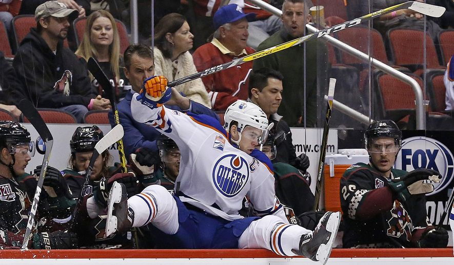 Edmonton Oilers center Connor McDavid leaps into the Arizona Coyotes bench area during the second period of an NHL hockey game Friday, Nov. 25, 2016, in Glendale, Ariz. (AP Photo/Ross D. Franklin)