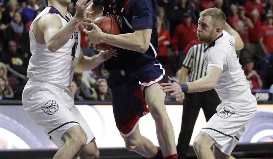 Arizona's Lauri Markkanen drives through Butler's Andrew Chrabascz, left, and Tyler Lewis, right, during the first half of an NCAA college basketball game Friday, Nov. 25, 2016, in Las Vegas. (AP Photo/John Locher)