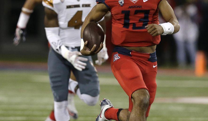 Arizona quarterback Brandon Dawkins runs for a touchdown during the first half of an NCAA college football game against Arizona State, Friday, Nov. 25, 2016, in Tucson, Ariz. (AP Photo/Rick Scuteri)