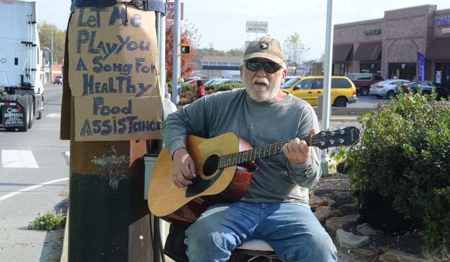 ADVANCE FOR WEEKEND EDITIONS, NOV. 26-27 - In this Nov. 15, 2016 photo, Navy veteran Kevin Morgan plays guitar on the side of a busy street in Clarksville, Tenn., to support himself. (Pranaav Jadhav/The Leaf-Chronicle via AP)