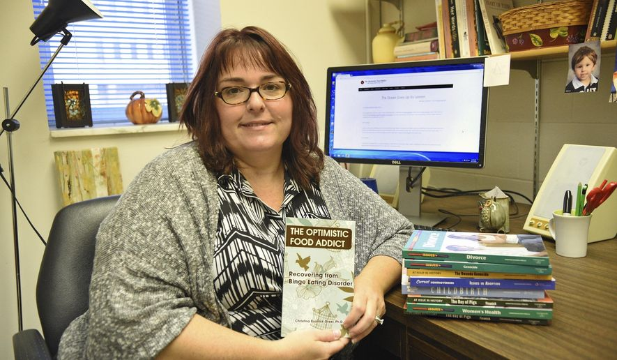 ADVANCE FOR WEEKEND EDITIONS - In this Thursday, Oct. 13, 2016, photo, Dr. Christina Fisanick-Greer holds her most recent book, released in October, that deals with her life as a binge eater and her recovery, in her office at California University in California, Pa. (Celeste Van Kirk/Observer-Reporter via AP)
