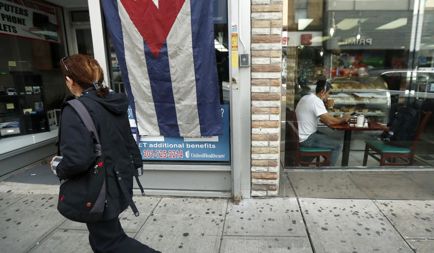 A Cuban flag adorns a business as a pedestrian walks by and a patron eats, Saturday, Nov. 26, 2016, in Union City, N.J. Business in a bustling shopping street are donning Cuban flags as news of Fidel Castro's passing spread. (AP Photo/Julio Cortez)