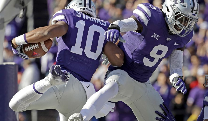 Kansas State defensive back Donnie Starks (10) celebrates with linebacker Elijah Lee (9) after Starks made an interception and scored a touchdown during the first half of an NCAA college football game Saturday, Nov. 26, 2016, in Manhattan, Kan. (AP Photo/Charlie Riedel)