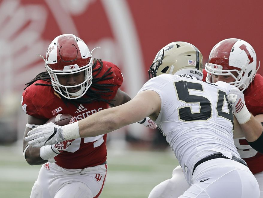 Indiana's Devine Redding, left, runs past Purdue's Jake Replogle during the first half of an NCAA college football game Saturday, Nov. 26, 2016, in Bloomington, Ind. (AP Photo/Darron Cummings)