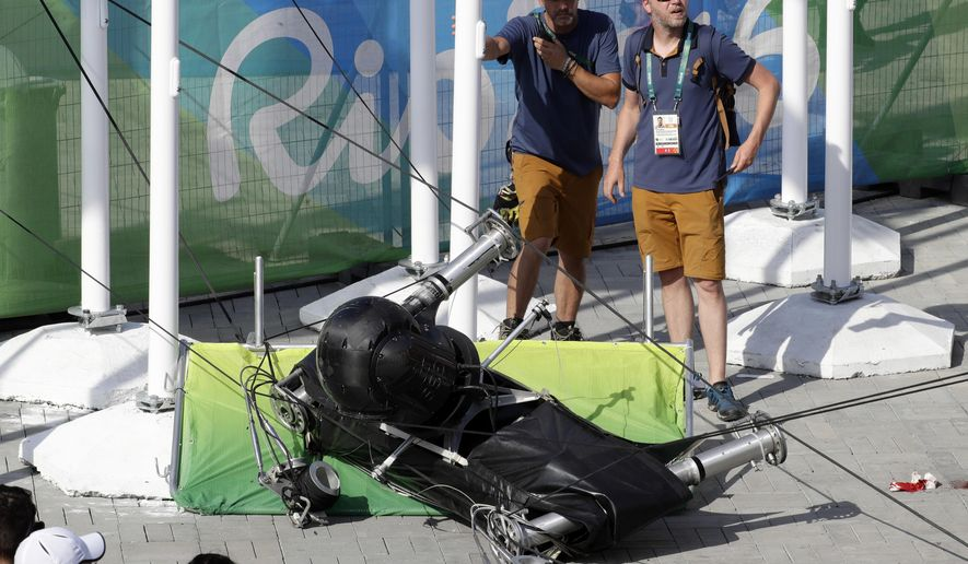 FILE - In this Aug. 15, 2016 file photo, an overhead camera that fell from wires suspending it over Olympic Park lays on the ground at the Summer Games in Rio de Janeiro, Brazil. A police investigation report released Friday, Nov. 25, 2016 says negligence was a factor when the overhead camera crashed to the ground three months ago, injuring eight people. (AP Photo/Robert F. Bukaty, File)