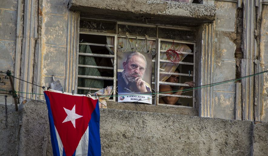 A picture of the late Fidel Castro and a Cuban flag decorate a home in Havana, Cuba, Sunday, Nov. 27, 2016. Cuba is observing nine days of mourning for the former president who ruled Cuba for half a century. (AP Photo/Desmond Boylan)