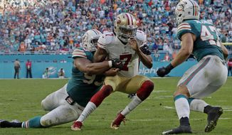 San Francisco 49ers quarterback Colin Kaepernick (7) is tackled by Miami Dolphins defensive tackle Ndamukong Suh (93) near the end zone, during the second half of an NFL football game, Sunday, Nov. 27, 2016, in Miami Gardens, Fla. To the right is Miami Dolphins middle linebacker Kiko Alonso (47). The Dolphins defeated the 49ers 31-24. (AP Photo/Lynne Sladky)