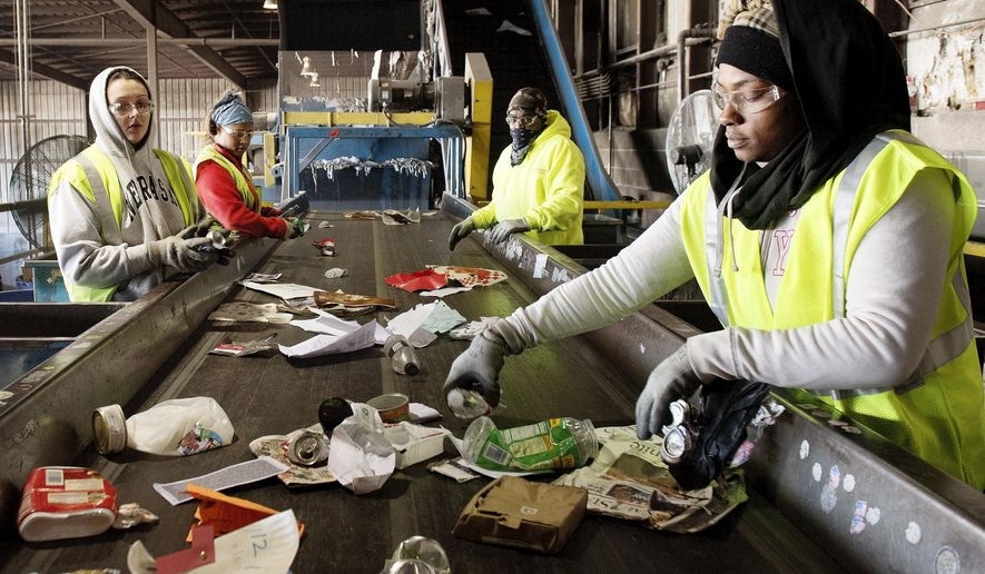 In this Nov. 16, 2016 photo, Mary Johnson, right, and her fellow employees sort items on a conveyor belt at the Mid-America Recycling plant, in Lincoln, Neb. (Francis Gardler  /The Journal-Star via AP)