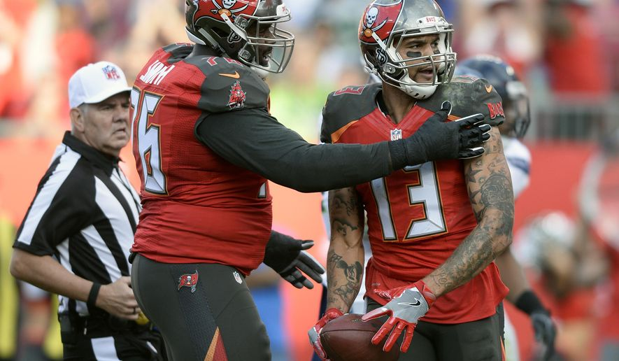 Tampa Bay Buccaneers wide receiver Mike Evans (13) celebrates his 3-yard touchdown reception with offensive tackle Donovan Smith (76) during the first quarter of an NFL football game against the Seattle Seahawks Sunday, Nov. 27, 2016, in Tampa, Fla. (AP Photo/Jason Behnken)
