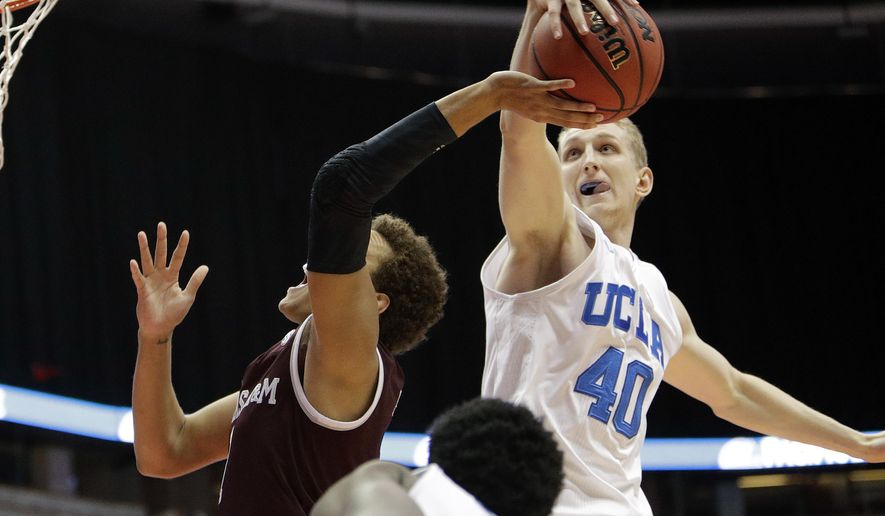 Texas A&M's DJ Hogg, left, gets his shot blocked by UCLA's Thomas Welsh during the first half of an NCAA college basketball game in the Wooden Legacy tournament Sunday, Nov. 27, 2016, in Anaheim, Calif. (AP Photo/Jae C. Hong)