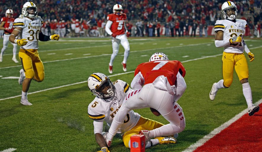 Wyoming cornerback Rico Gafford (5) fails to stop New Mexico running back Teriyon Gipson for scoring a touchdown during the first half of an NCAA college football game in Albuquerque, N.M., Saturday, Nov. 26, 2016. (AP Photo/Andres Leighton)