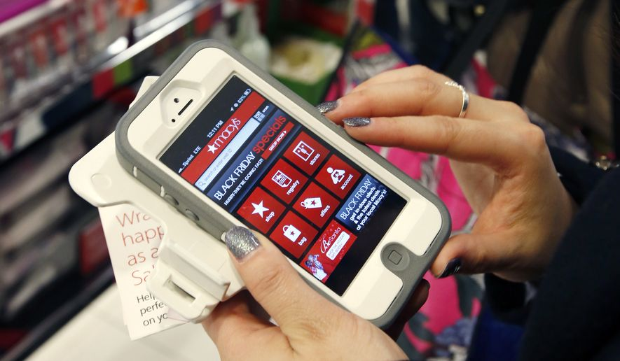 In this Friday, Nov. 23, 2012, file photo, Tashalee Rodriguez, of Boston, uses a smartphone app while shopping at Macy's in downtown Boston. Shoppers are flocking online Monday, Nov. 28, 2016, as Cyber Monday sales hit their peak. (AP Photo/Michael Dwyer, File)