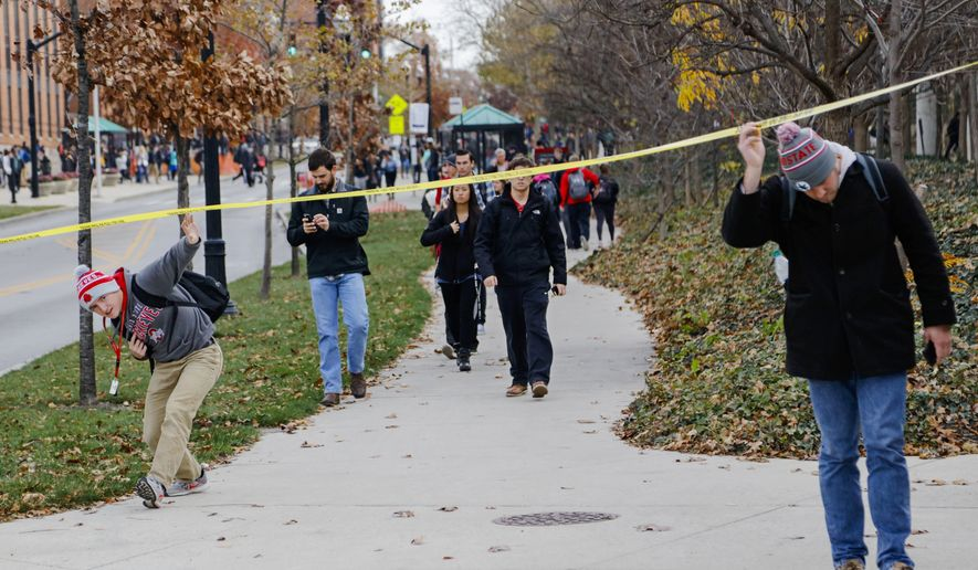 Ohio State students duck under police tape after a shelter-in-place notification was lifted following an attack Monday, Nov. 28, 2016, at Ohio State University in Columbus, Ohio. (Joshua A. Bickel/The Columbus Dispatch via AP)