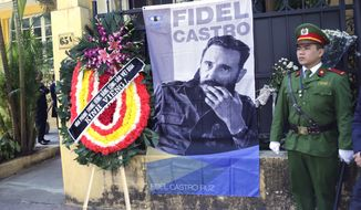 A Vietnamese policeman stands guard as a wreath and an image of the late Cuban President Fidel Castro are placed at the Cuban embassy in Hanoi, Vietnam, Monday, Nov. 28, 2016. Castro, who led his bearded rebels to victorious revolution in 1959, embraced Soviet-style communism and defied the power of 10 U.S. presidents during his half-century of rule in Cuba, died on Friday at age 90. (AP Photo/Tran Van Minh)