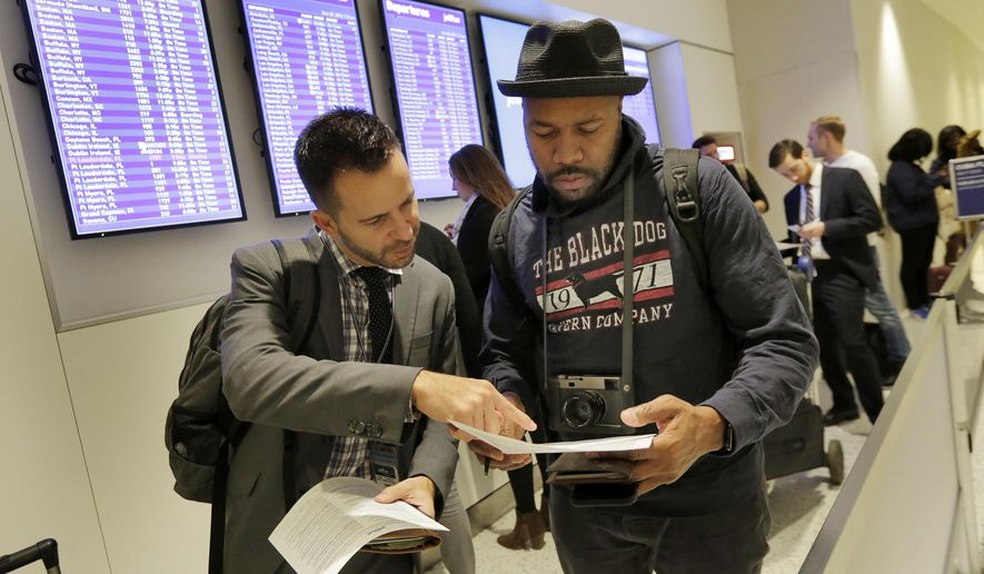 David McGraw, left, and Derrick Jones, both from New York, look over their paperwork while waiting to check in for JetBlue's inaugural flight from New York's John F. Kennedy International Airport to Havana, Monday, Nov. 28, 2016. (AP Photo/Richard Drew)