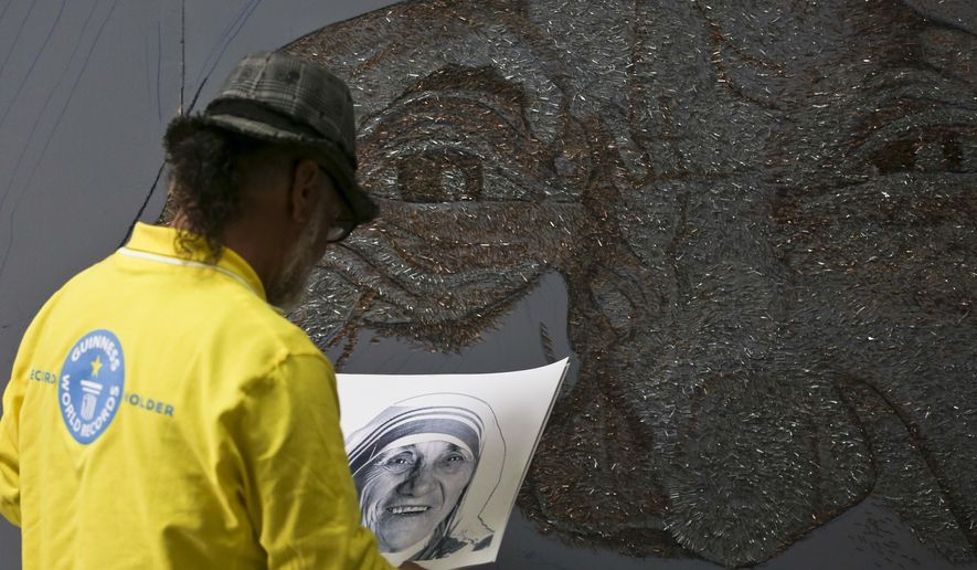 In this photo taken on Tuesday, Nov. 8, 2016, Albanian artist Saimir Strati works on a mosaic portrait of Mother Teresa, at the Kosovo National Museum building in Pristina. Strati has built a portrait of Mother Teresa using staples, in a call for European countries to stop raising fences to shut their borders to refugees. (AP Photo/Visar Kryeziu)