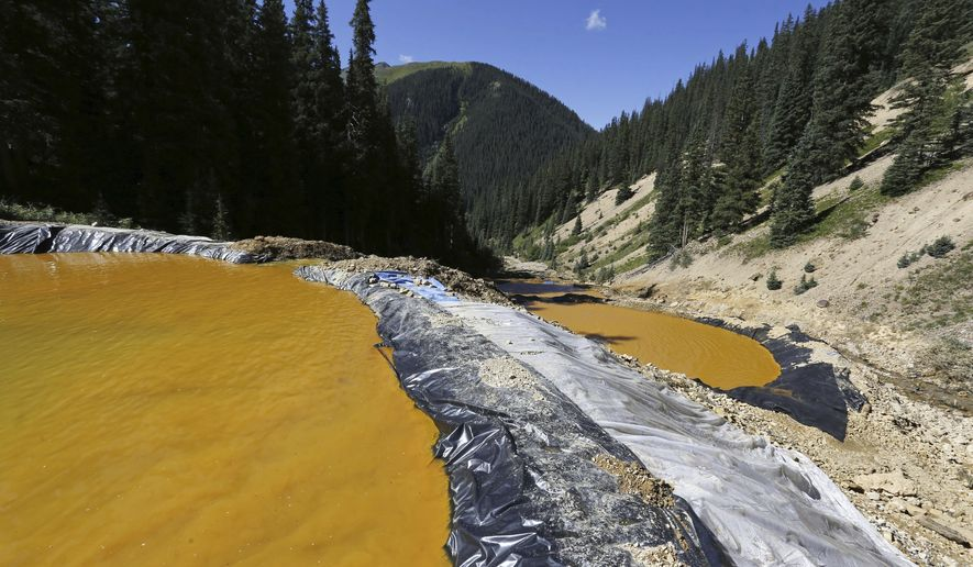 In this Aug. 14, 2015, file photo, water flows through a series of sediment retention ponds built to reduce heavy metal and chemical contaminants from the Gold King Mine wastewater accident in the spillway about 1/4 mile downstream from the mine outside Silverton, Colo. On Monday, Nov. 28, 2016, the U.S. Supreme Court asked the Justice Department to weigh in on New Mexico's lawsuit against Colorado over the Gold King mine waste spill that polluted rivers in both states and in Utah. (AP Photo/Brennan Linsley, File)