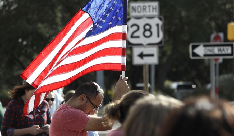 An onlooker holds a flag as he and others pay their respects as the funeral procession for San Antonio police detective Benjamin Marconi passes by en route to services, Monday, Nov. 28, 2016, in San Antonio. Marconi was fatally shot during a traffic stop near police headquarters on Nov. 20. (AP Photo/Eric Gay)