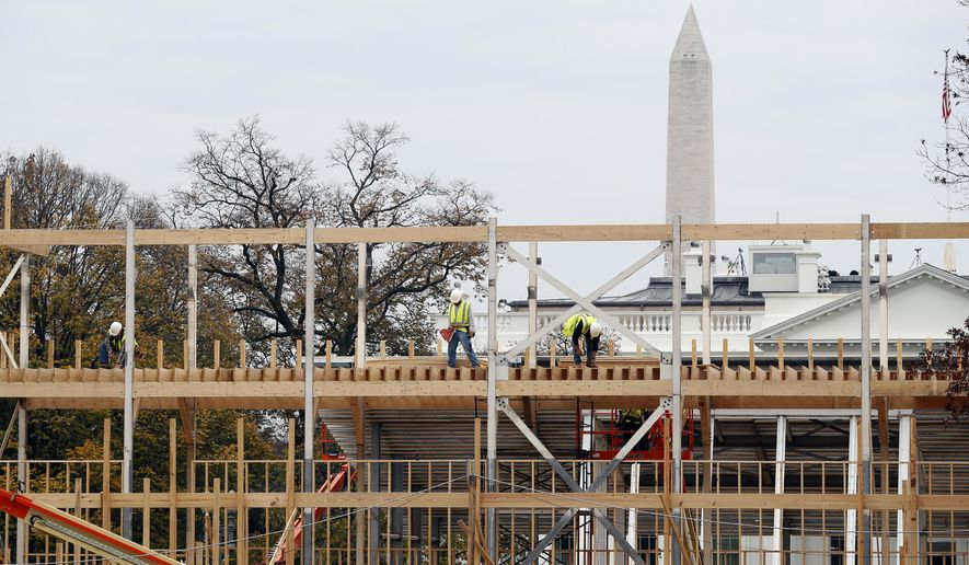 Construction continues on the presidential reviewing stand on Pennsylvania Avenue in Washington, Friday, Nov. 25, 2016, looking toward the White House and the Washington Monument. The reviewing stand is where then President Donald Trump will view the inaugural parade on Jan. 20, 2017. (AP Photo/Alex Brandon)