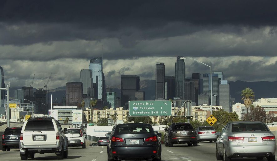 Trailing bands of clouds pass over downtown Los Angeles on Sunday, Nov. 27, 2016. The National Weather Service is warning travelers about heavy winds and potential blowing snow on busy Interstate 5 in Southern California. (AP Photo/John Antczak)