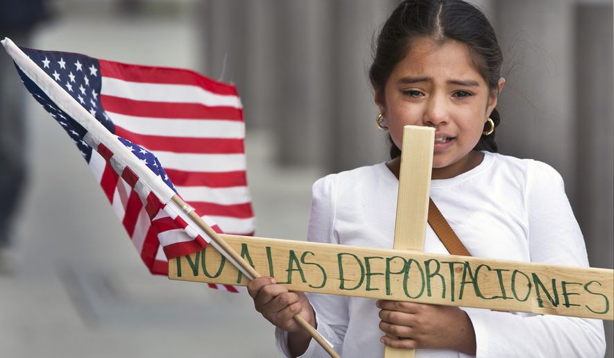 """Yesenia Del Carmen 8, carries a cross reading """"No to the Deportations,"""" """"as she and her grandmother join an immigrant-rights supporters """"Procession of the Cross"""" walk, led by U.S.-born children from the Federal building to the Cathedral of Our Lady of the Angels in Los Angeles, Friday, Apr. 18, 2014. Immigrants urged the Obama administration today to stop deportations that they said are splitting up families. Del Carmen worries her father could be deported while at work. (AP Photo/Damian Dovarganes)"""