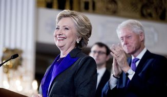 Hillary Clinton, accompanied by former President Bill Clinton, right, pauses while speaking to staff and supporters at the New Yorker Hotel in New York, Nov. 9, 2016. Hillary Clinton introduced singer and UNICEF Goodwill Ambassador Katy Perry on Tuesday, Nov. 29, at the annual event in New York. (AP Photo/Andrew Harnik) ** FILE **