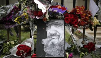 A caricature depicting Cuba's late leader Fidel Castro is surrounded by flowers at a makeshift memorial outside the Cuban embassy in Buenos Aires, Argentina, Monday, Nov. 28, 2016. Castro, who led a rebel army to improbable victory, embraced Soviet-style communism and defied the power of 10 U.S. presidents during his half century rule of Cuba, died late Friday at age 90. (AP Photo/Victor R. Caivano)