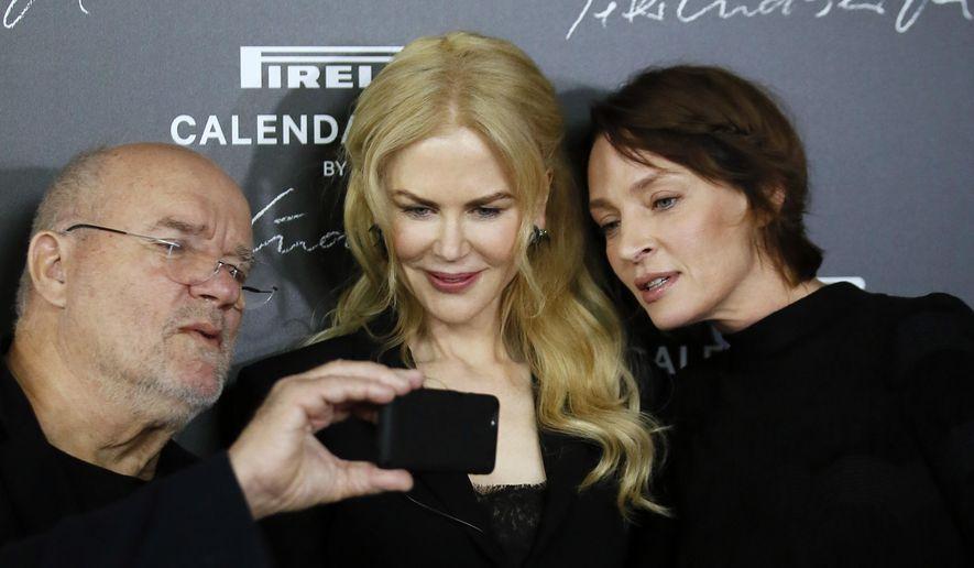 Photographer Peter Lindbergh, left, shows his phone to Nicole Kidman, center, and Uma Thurman during a photocall to unveil the Pirelli 2017 calendar by Peter Lindbergh in Paris, Tuesday, Nov. 29, 2016. (AP Photo/Francois Mori)