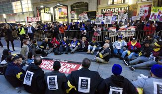 A crowd of about 350 protesters stand on Broadway in front of a McDonald's restaurant, Tuesday, Nov. 29, 2016, in New York. About 25 of the chanting minimum-wage protesters, foreground, were arrested. The event was part of the National Day of Action to Fight for $15. The campaign seeks higher hourly wages, including for workers at fast-food restaurants and airports. (AP Photo/Mark Lennihan)