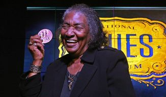 Frances Johnson, widow of jazz and blues pianist Johnnie Johnson, holds up the Congressional Gold Medal that was awarded to her late husband on Monday, Nov. 28, 2016, during a ceremony at the National Blues Museum in downtown St. Louis. Johnnie Johnson died in St. Louis in 2005.  ( J.B. Forbes/St. Louis Post-Dispatch via AP)
