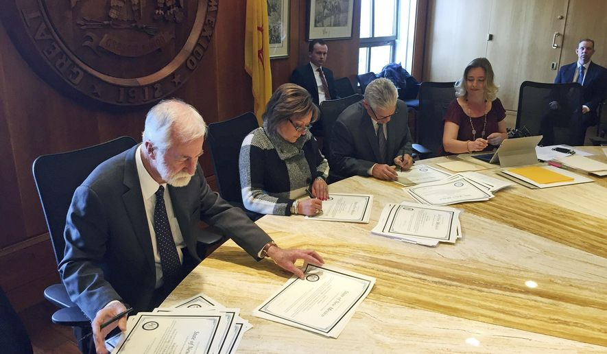 Members of the New Mexico State Canvassing Board sign certificates of election in Santa Fe Tuesday, Nov. 29, 2016. From left, New Mexico Supreme Court Chief Justice Charles Daniels, Gov. Susana Martinez and Secretary of State Brad Winter certify results of the Nov. 8 election and ordered recounts in state legislative races. The three-member board was accompanied by State Elections Director Kari Fresquez, right. (AP Photo/Morgan Lee)