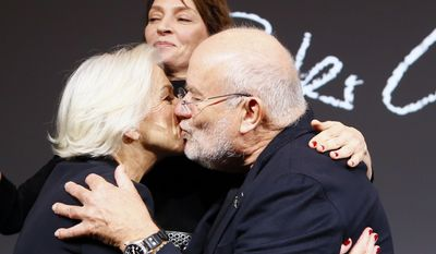 Photographer Peter Lindbergh, right, kisses actress Helen Mirren, left, as Uma Thurman looks on during a photocall to unveil the Pirelli 2017 calendar by Peter Lindbergh in Paris, Tuesday, Nov. 29, 2016. (AP Photo/Francois Mori)
