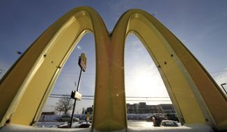 Cars drive past the McDonald's Golden Arches logo at a McDonald's restaurant in Robinson Township, Pa., in this Jan. 21, 2014, file photo. (AP Photo/Gene J. Puskar, File)