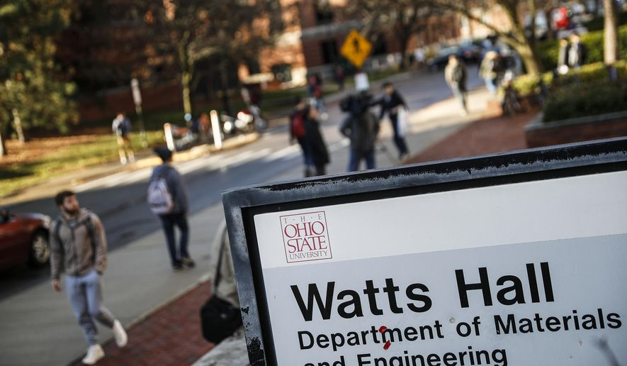Students pass Watts Hall as they return to class following an attack at The Ohio State University campus the previous day, Tuesday, Nov. 29, 2016, in Columbus, Ohio. Investigators are looking into whether a car-and-knife attack at Ohio State University that injured several people was an act of terror.  (AP Photo/John Minchillo)