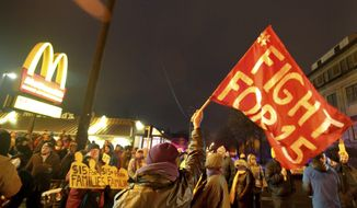 Protesters gather outside a McDonald's during a demonstration for higher wages on Tuesday, Nov. 29, 2016 in Minneapolis.   The protest was part of the National Day of Action to Fight for $15. The campaign seeks higher hourly wages, including for workers at fast-food restaurants and airports.  (Joles, David/Star Tribune via AP)