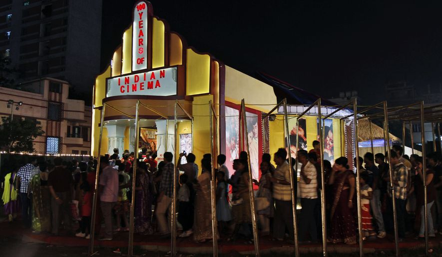People stand in a queue to enter a movie theater in Kolkata, India, on Oct. 11, 2013. (Associated Press) **FILE**