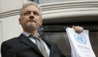WikiLeaks founder Julian Assange holds a U.N. report as he speaks on the balcony of the Ecuadorian Embassy in London in this Friday, Feb. 5, 2016, file photo. (AP Photo/Frank Augstein, File)
