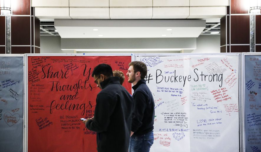 Students mill about The Ohio State University student union Tuesday, Nov. 29, 2016, as a message board covered in community reactions stands in the main hall following an attack at on campus the previous day,  in Columbus, Ohio. Investigators are looking into whether a car-and-knife attack at Ohio State University that injured several people was an act of terror by a student who had once criticized the media for its portrayal of Muslims. (AP Photo/John Minchillo)