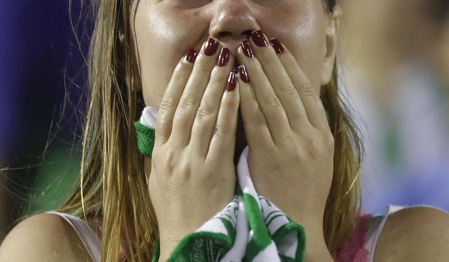 A fan of Brazil's soccer team Chapecoense mourns during a gathering inside Arena Conda stadium in Chapeco, Brazil, Tuesday, Nov. 29, 2016. A chartered plane carrying the Brazilian soccer team Chapecoense to the biggest match of its history crashed into a Colombian hillside and broke into pieces on Tuesday, killing most passengers, Colombian officials said. (AP Photo/Andre Penner)