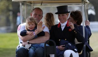 In this May 6, 2016 photo, Britain's Queen Elizabeth II's granddaughter Zara Tindall and her husband Mike Tindall ride in a buggy with their daughter Mia, at Badminton horse trials in Badminton, England. Officials say the couple are expecting their second child in late spring 2017. (Steve Parsons/PA via AP/File)