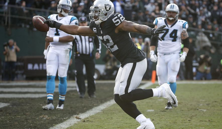 FILE - In this Sunday, Nov. 27, 2016, file photo, Oakland Raiders defensive end Khalil Mack (52) scores a touchdown after intercepting a pass by Carolina Panthers quarterback Cam Newton, left rear, during the first half of an NFL football game in Oakland, Calif. After becoming the first player ever named a first-team All Pro at two positions in one season in 2015, Raiders pass rusher Khalil Mack is taking his game to another level this year. (AP Photo/Tony Avelar, File)