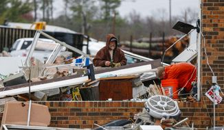 Gregg Jefferey, left, and his son Tyler help a family friend clean up their business at Rosalie Plaza after a possible tornado ripped through the town, Wednesday, Nov. 30, 2016, in Rosalie, Ala.  Storms that spawned deadly winds have dumped more than 2 inches of rain across much of north Alabama, causing floods after months of drought. (AP Photo/Butch Dill)